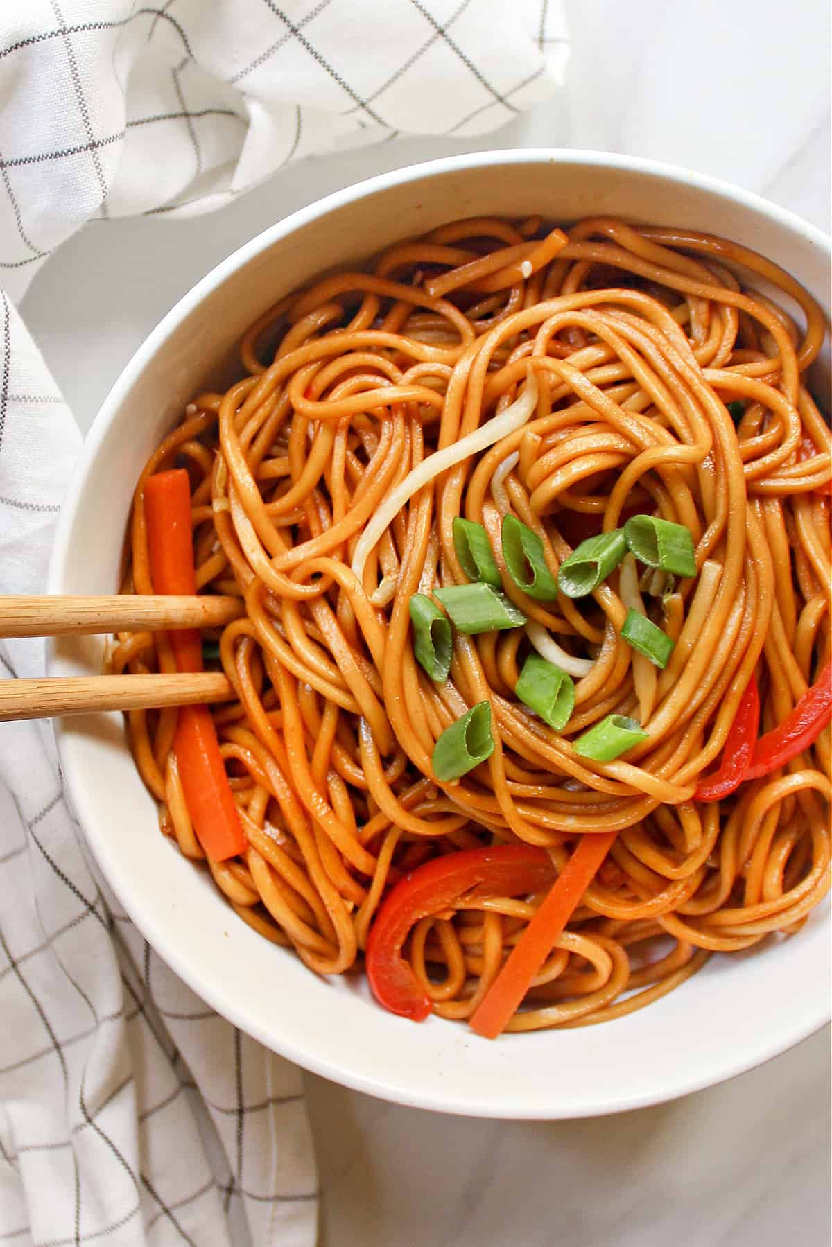 Overhead view of noodles in a white bowl with napkin on the side.