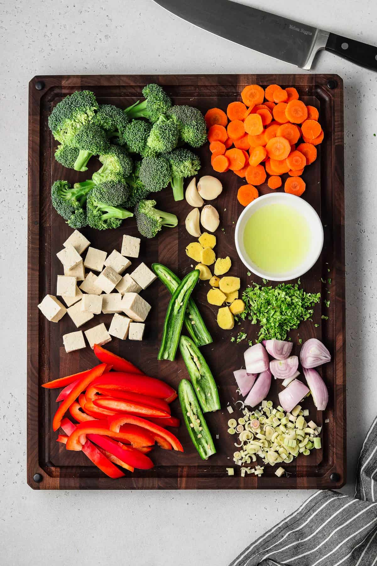 Cut vegetables on a wood cutting board with a napkin on the side.