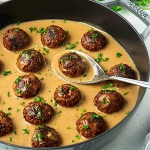 vegan Swedish meatballs in a gray pan filled with gravy