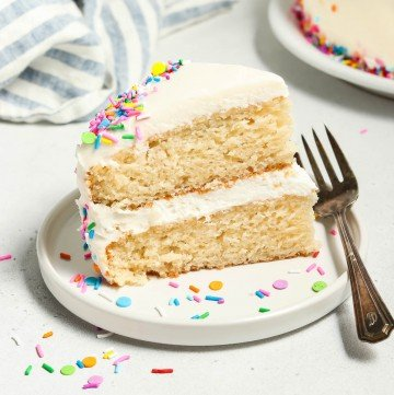 A slice of vegan vanilla cake on a white plate. Fork on the side.