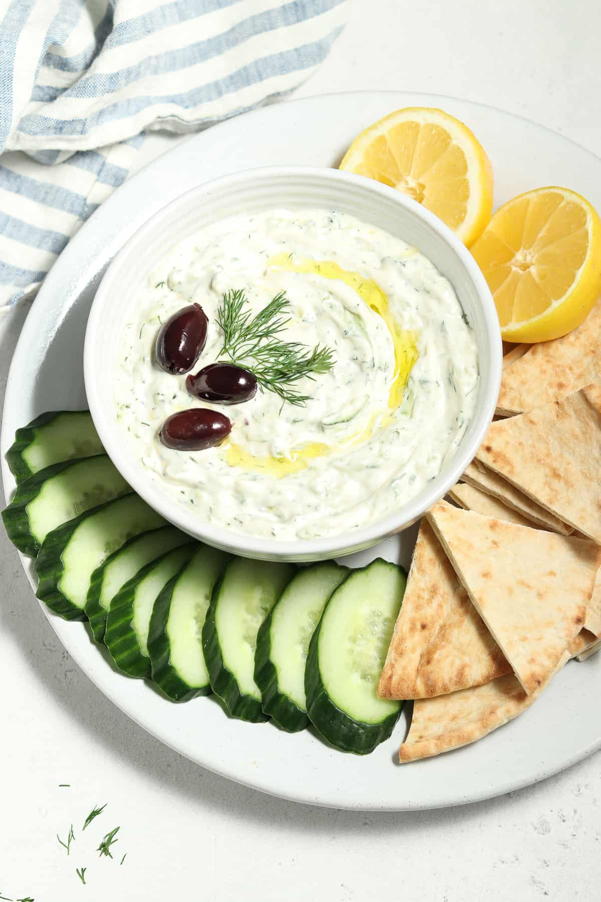 Overhead view of vegan tzatziki sauce in white bowl surrounded by pita slices and cucumber slices.
