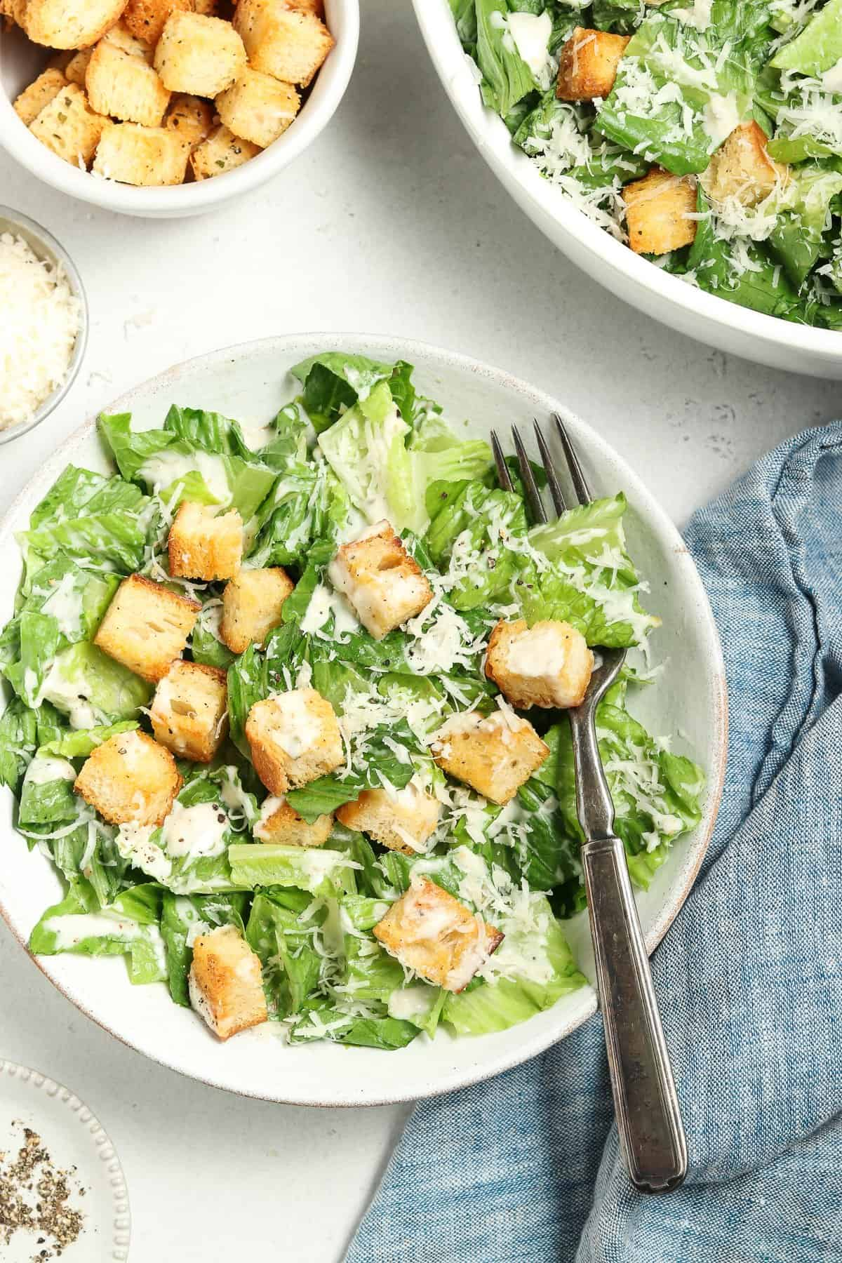 Overhead view of a vegan caesar salad in a white bowl with a blue napkin, pepper and croutons on the side.