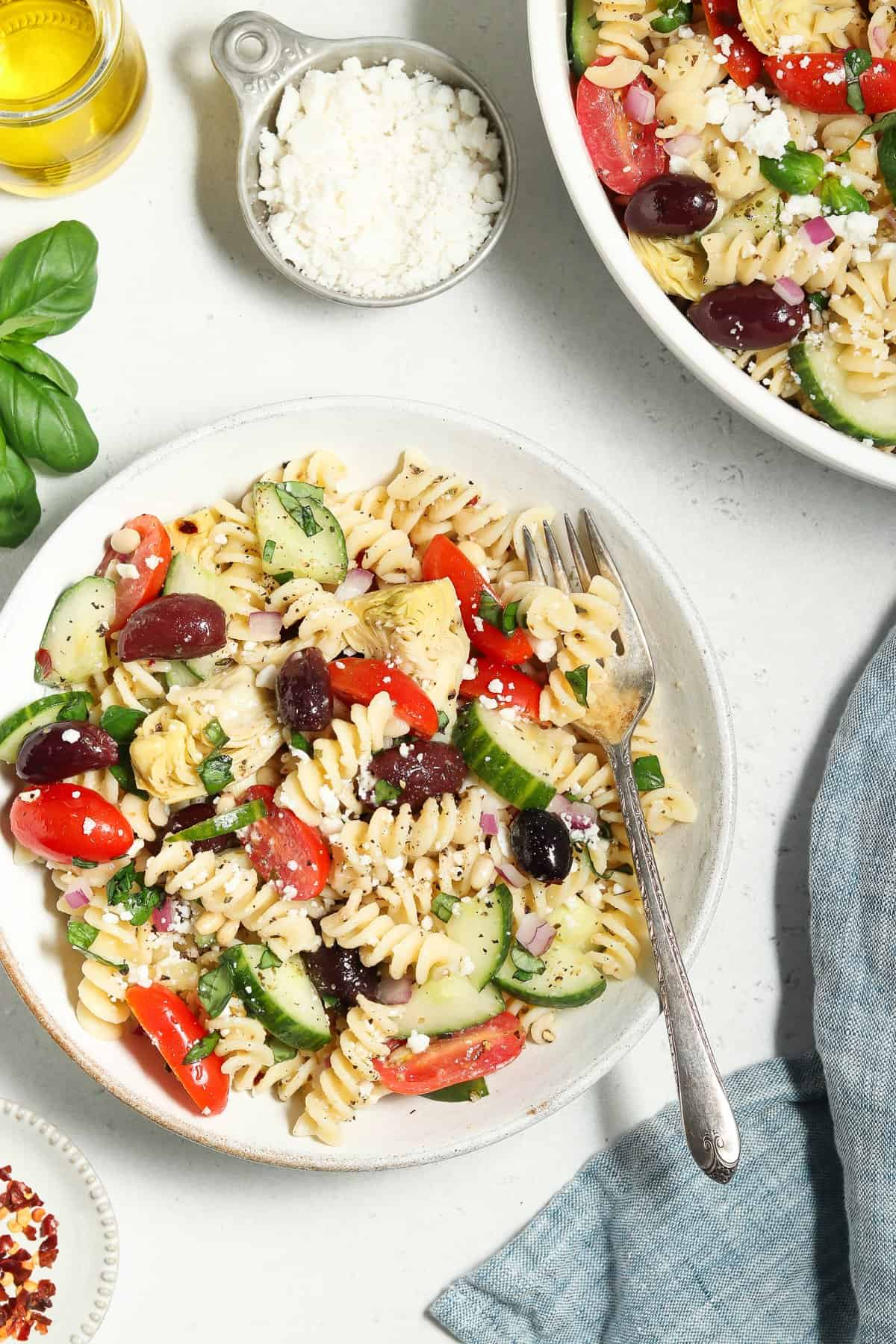 Overhead view of Mediterranean Pasta Salad in a small bowl and a larger bowl on the side. Blue napkin on the side.