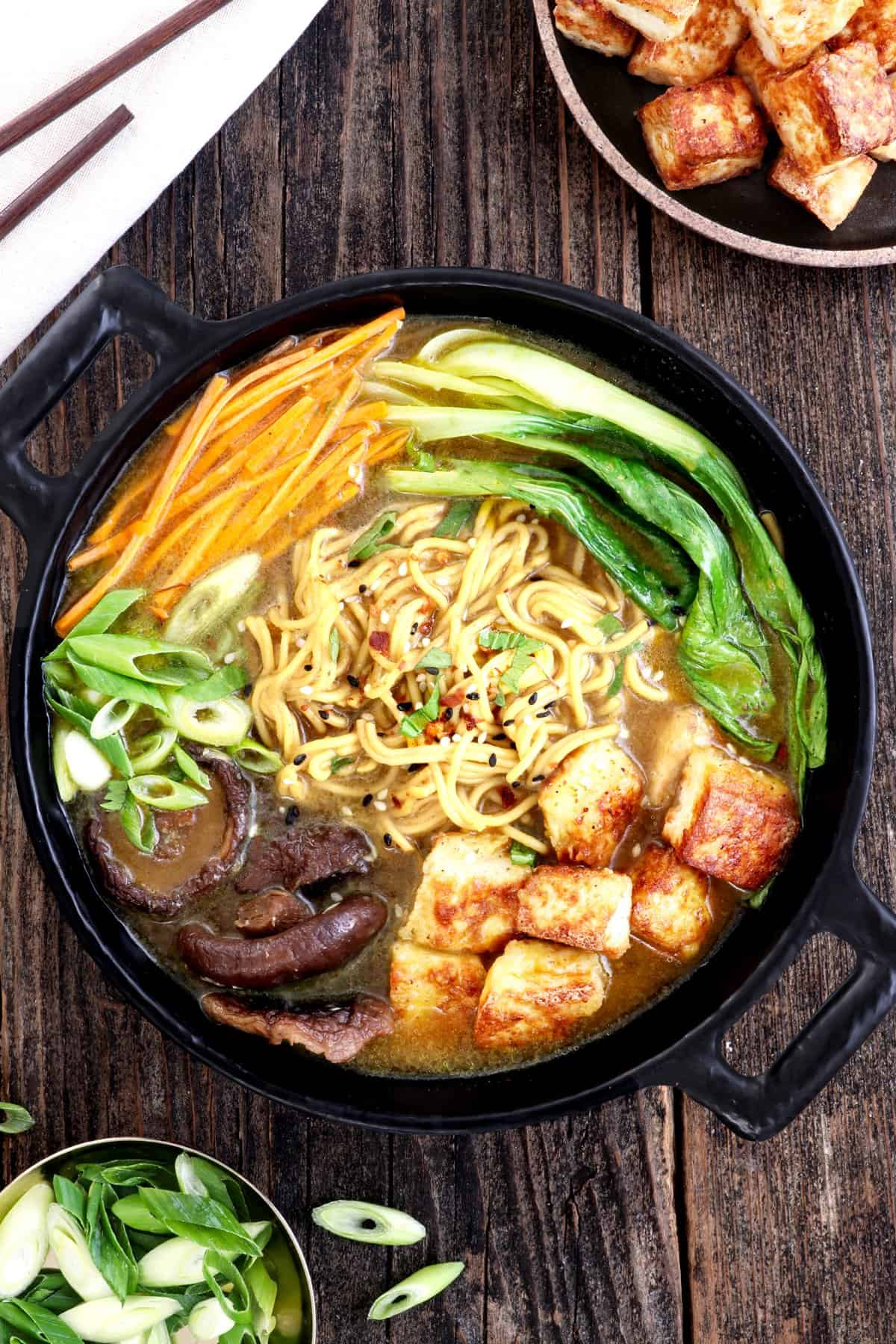 Overhead view of vegan ramen in a black bowl. Tofu and green onions on the side.