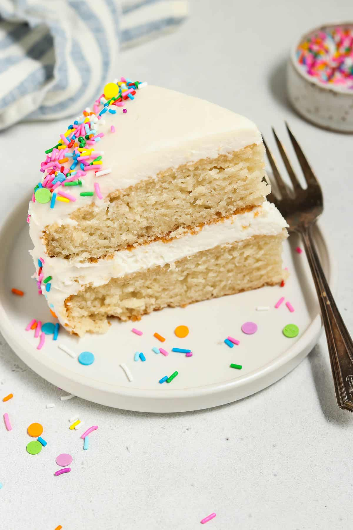 Overhead view of a slice of vegan vanilla cake on a plate. Sprinkles and fork on the side.