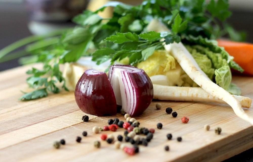 Hagyma, leveszöldségek, bors egy vágódeszkán