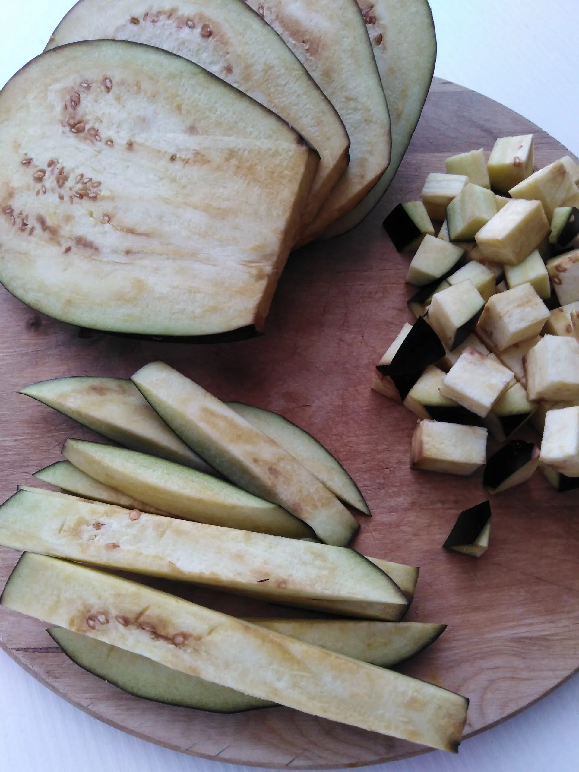 Halved, sliced and cubed eggplants on a wooden chopping board
