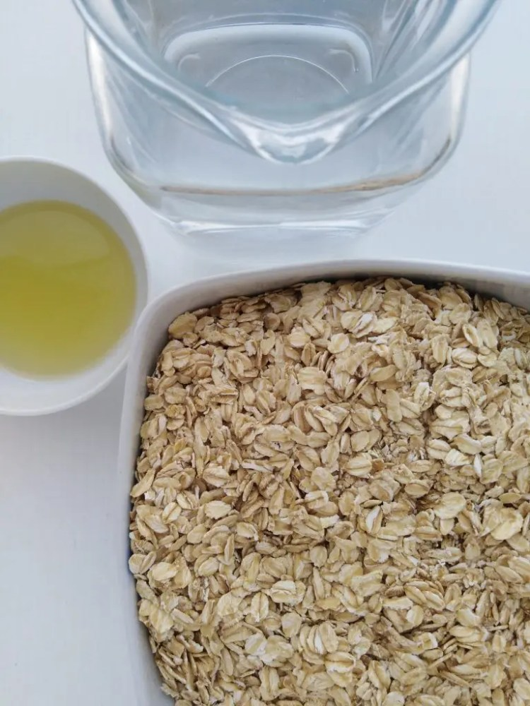 Ingrediets: water in a glass jar. oil in a dish and rolled oats in a bowl