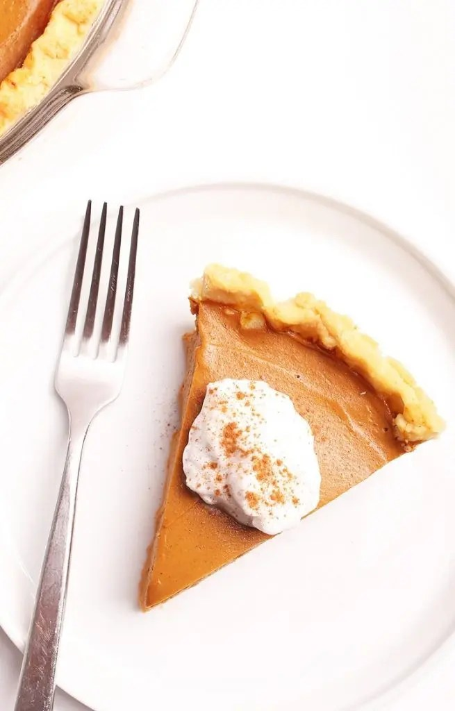 Slice of vegan thanksgiving pumpkin pie on a plate with a fork