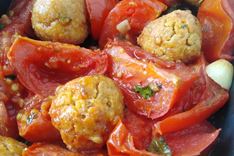 baking tray with chickpea balls and roasted tomatoes and garlic