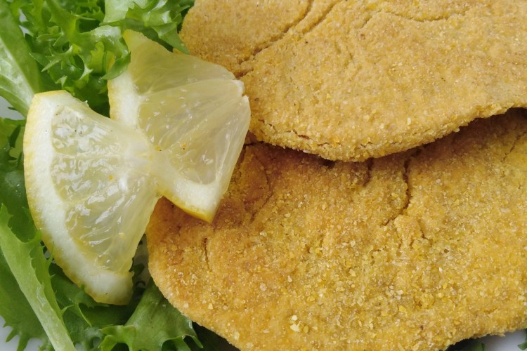 2 chickpea cutlets on a plate with some salad and lemon slices