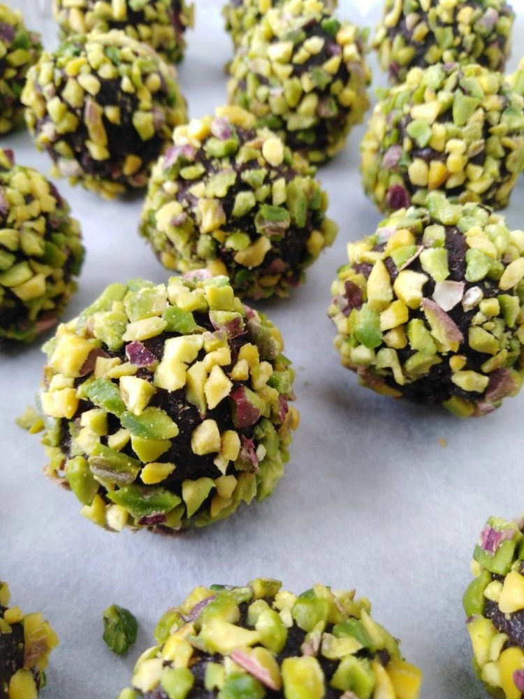 tray filled with vegan chocolate truffles with chickpeas covered in crushed pistachios