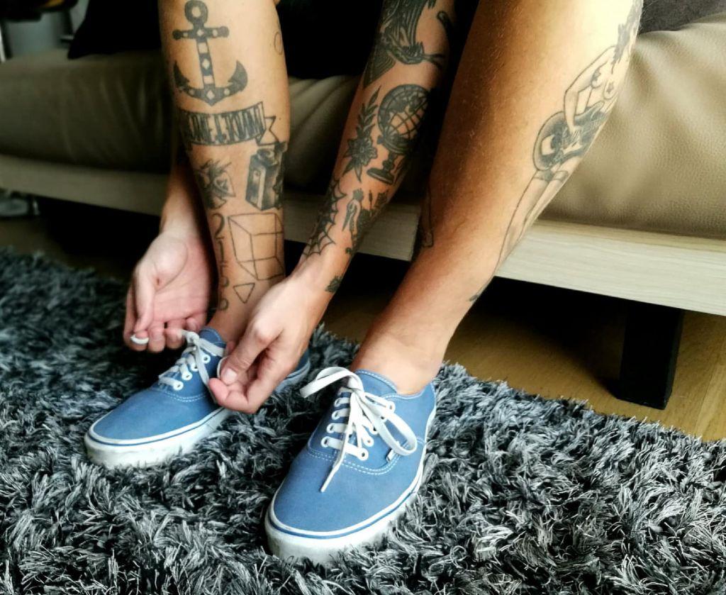 man tying blue vegan sneakers