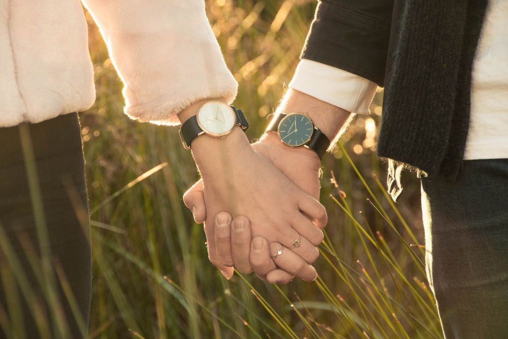 girl and guy holding hands wearing vegan watches