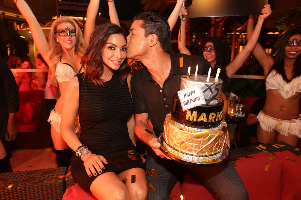 Mario Lopez gives his wife a kiss on the cheek at XS Nightclub