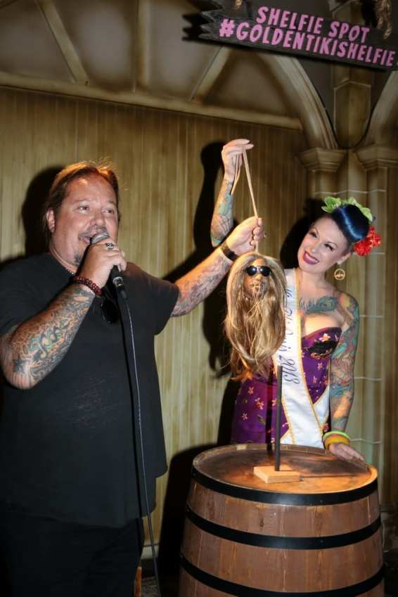Vince Neil holding up shrunken head for the crowd