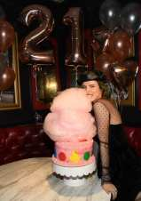 Bella Thorne takes a bite out of Sugar Factory's larger-than-life, red velvet cotton candy cake covered in pink icing
