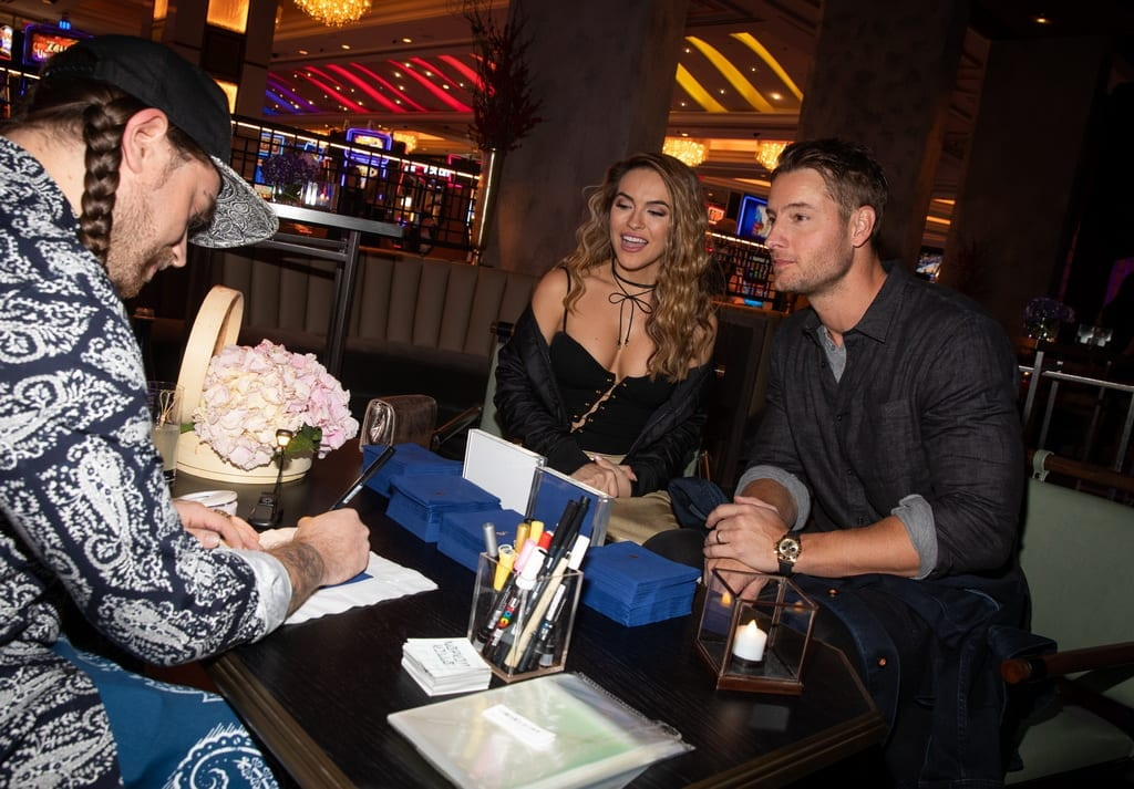 Justin Hartley and wife watch as Napkin Killa creates a signature drawing for them at the Mott 32 grand opening at The Venetian Resort Las Vegas, 12.28.18_Credit Erik Kabik