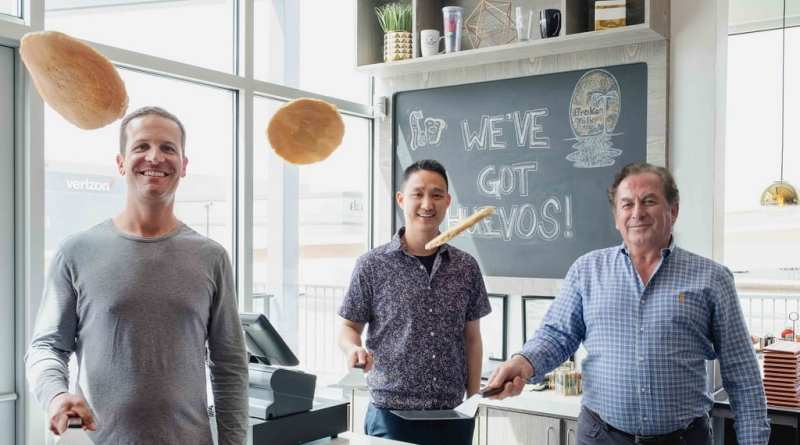 Right to left, Randy Corrigan, Barry Tu and John Gelastopoulos officially open the restaurant with oversized pancake flip.