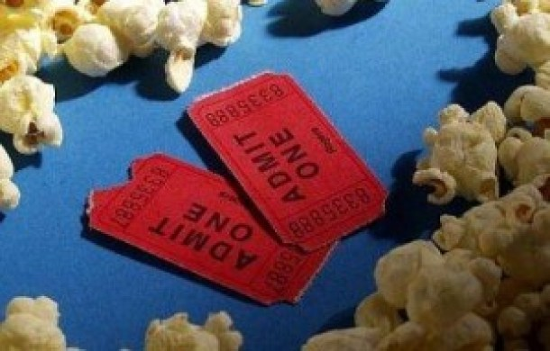 Two movie tickets surrounded by popcorn- regal cinemas