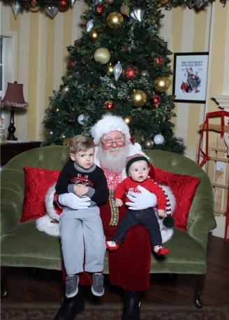Two small boys sitting with Santa in photo at Town Square