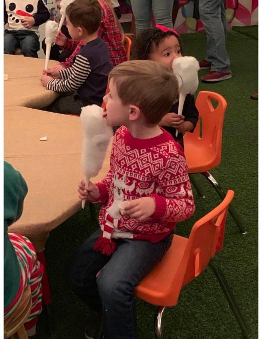 boy eating cotton candy at Operation North Pole at Tivoli Village