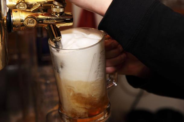 Bartender pouring large draft beer from tap