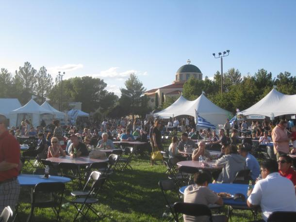 Beautiful sunny day pic of tents and scores of people sitting at tables enjoying the Greek Food Festival