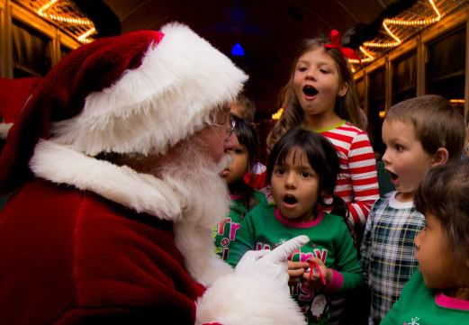 Santa on train, talking to children, all with their mouths open in awe.