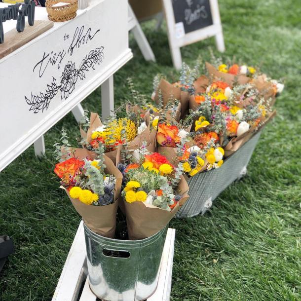 Fall colored flowers wrapped in paper in tin containers at craft sale
