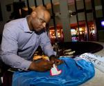 Warren Moon signs a jersey at HERAEA