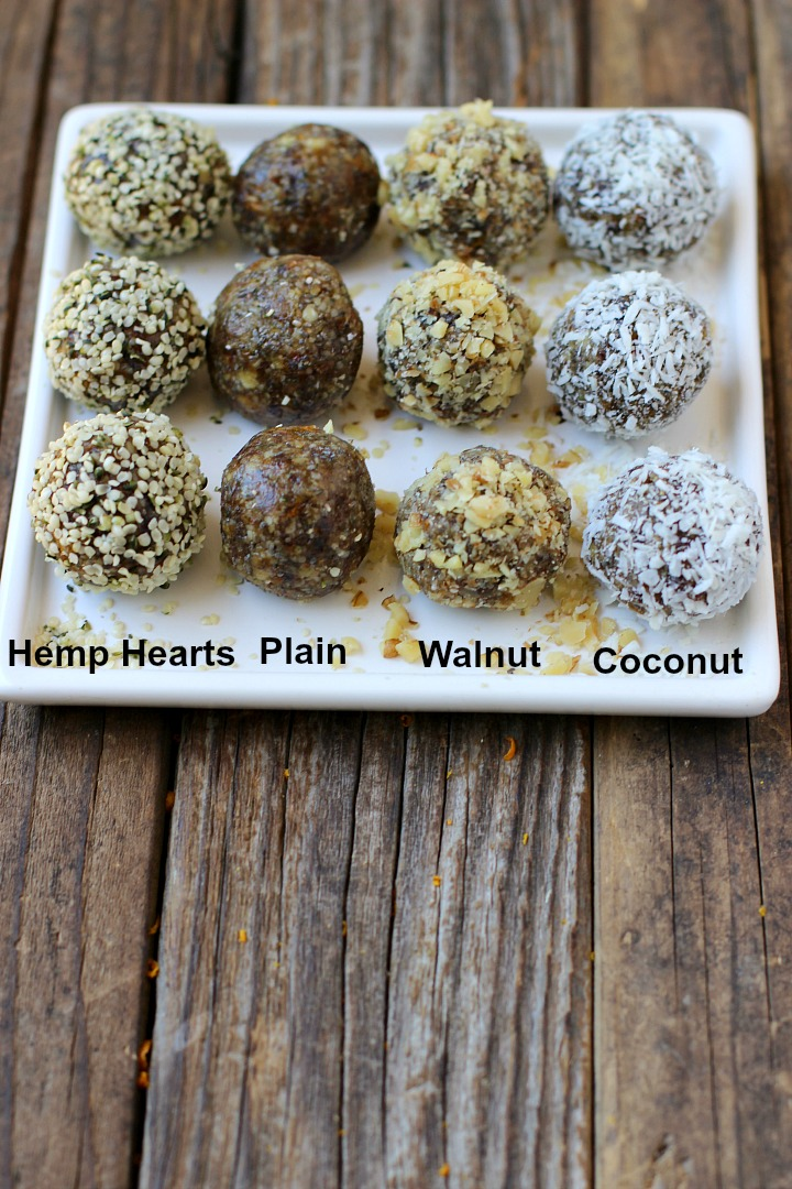 4 labeled rows of date balls on a white plate. 1 rolled in hemp hearts, 1 of plain ones, 1 rolled in walnuts and 1 rolled in coconut.