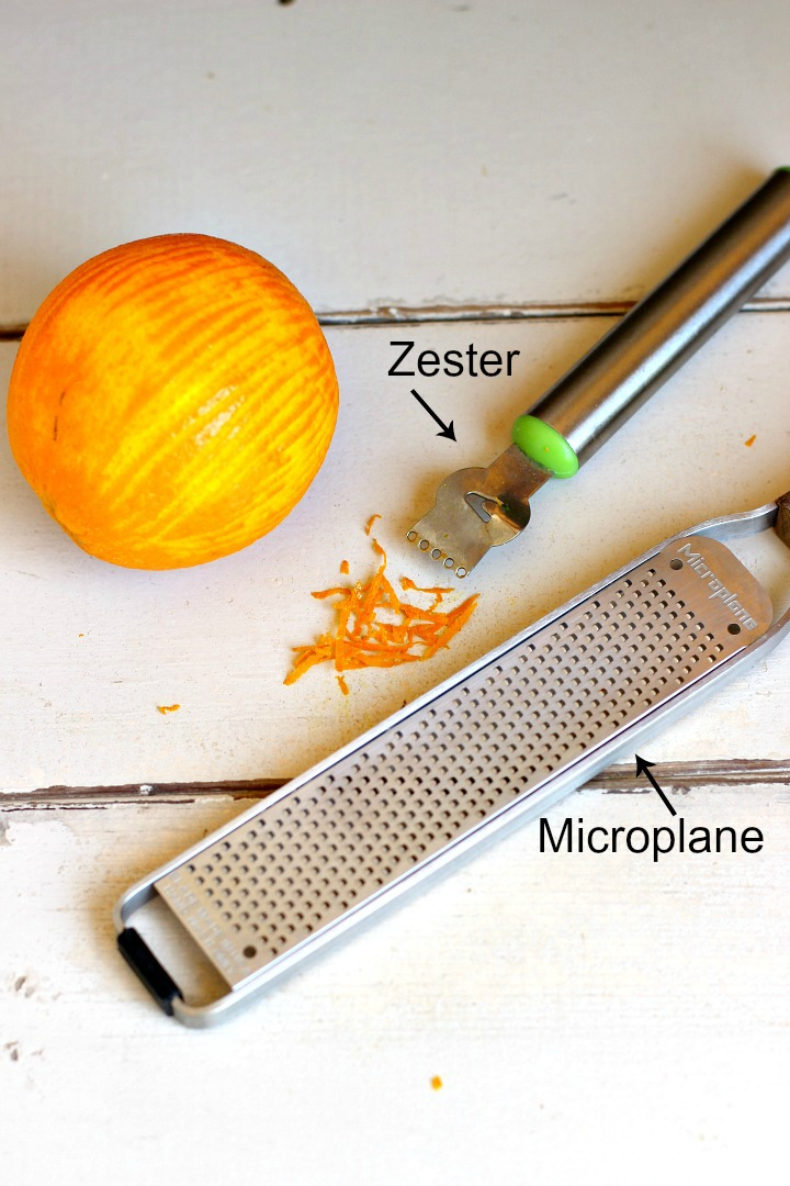 A zested orange on a white background with a zester tool and a microplane.