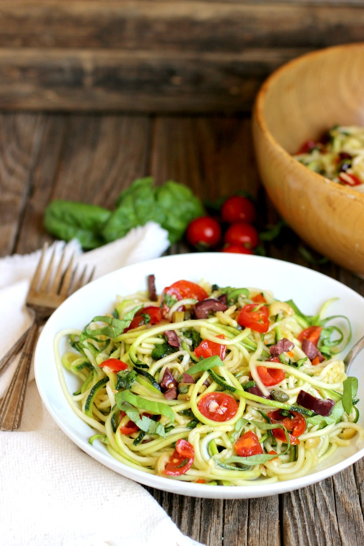 White bowl of Zucchini Noodle Salad with zucchini noodles, cherry tomatoes, kalamata olives, green olives, fresh basil and capers