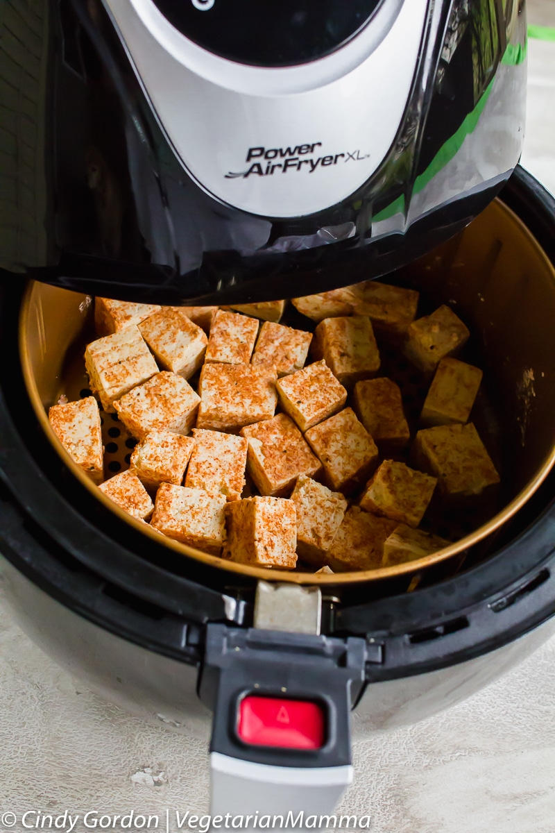 Tofu cubes being cooked in an air fryer