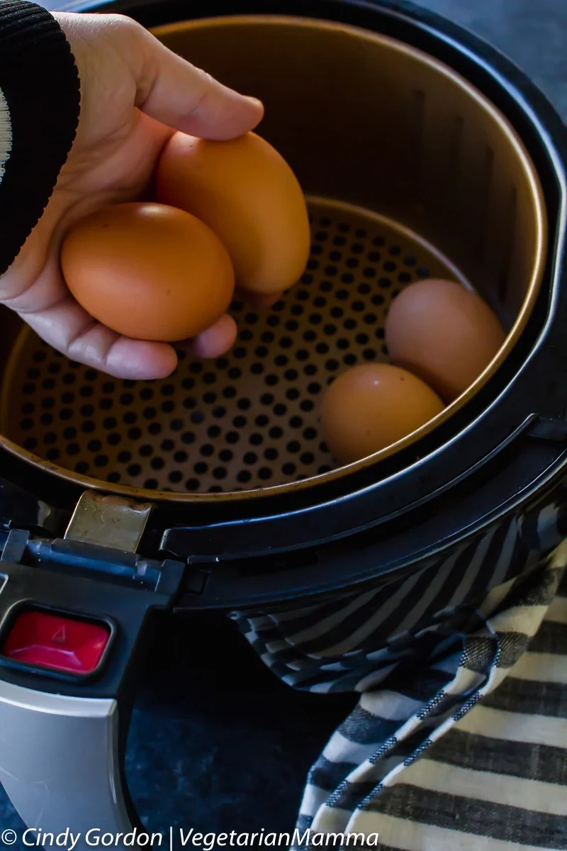 Eggs being placed into an air fryer basket