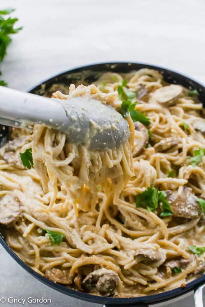 Metal tongs stirring spaghetti and mushrooms in vegan carbonara sauce to coat them evenly