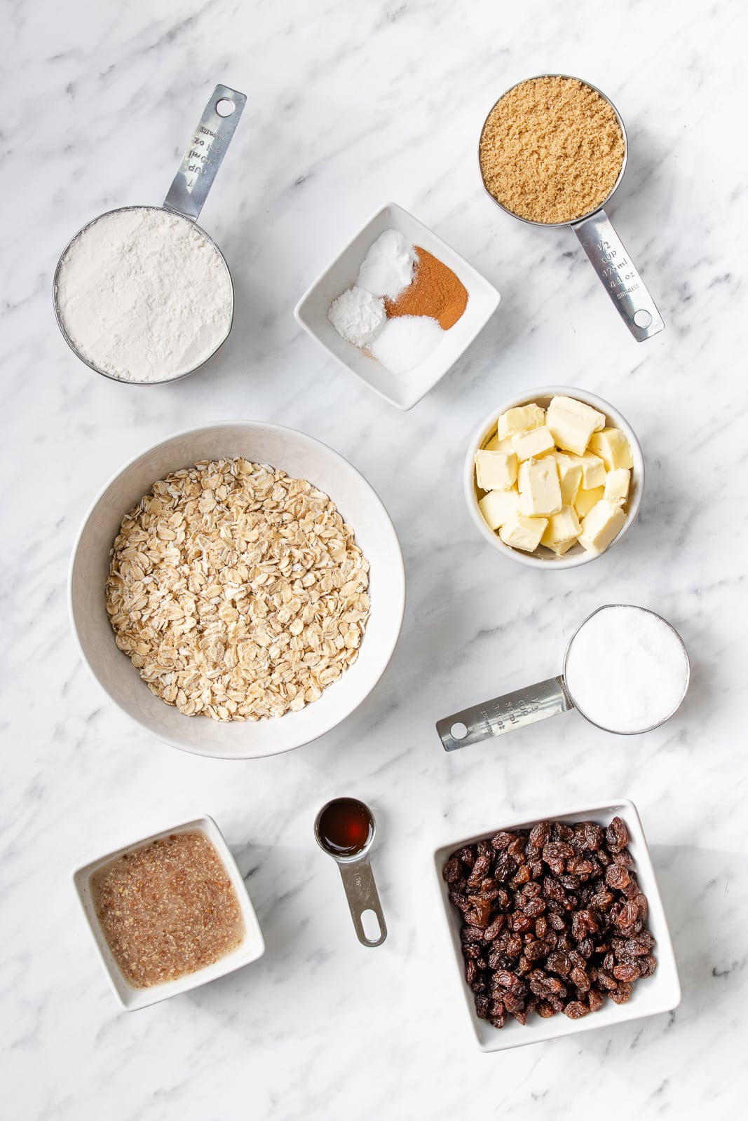 Bowls and measuring cups of brown sugar, caster sugar, gluten-free flour, butter, oats, and raisins
