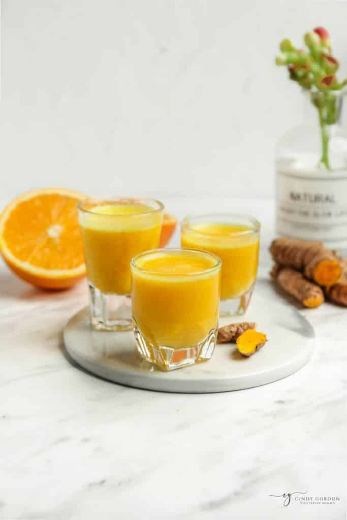 vertical angled shot of orange liquid in three glasses, with orange half to the left, fresh turmeric to the right