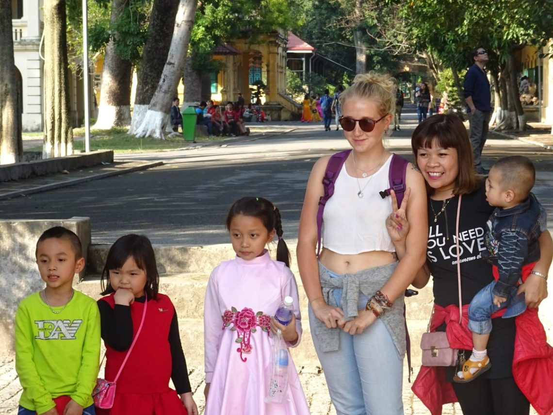 Vietnamese family with tourist posing for photo
