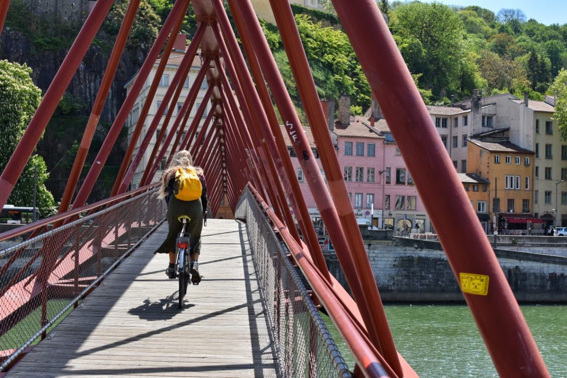 Girl cycling over red bridge in Lyon