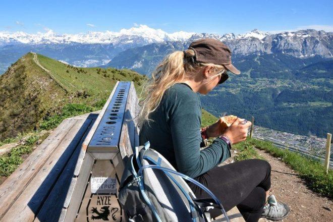 Girl on mountain eating vegan hiking food