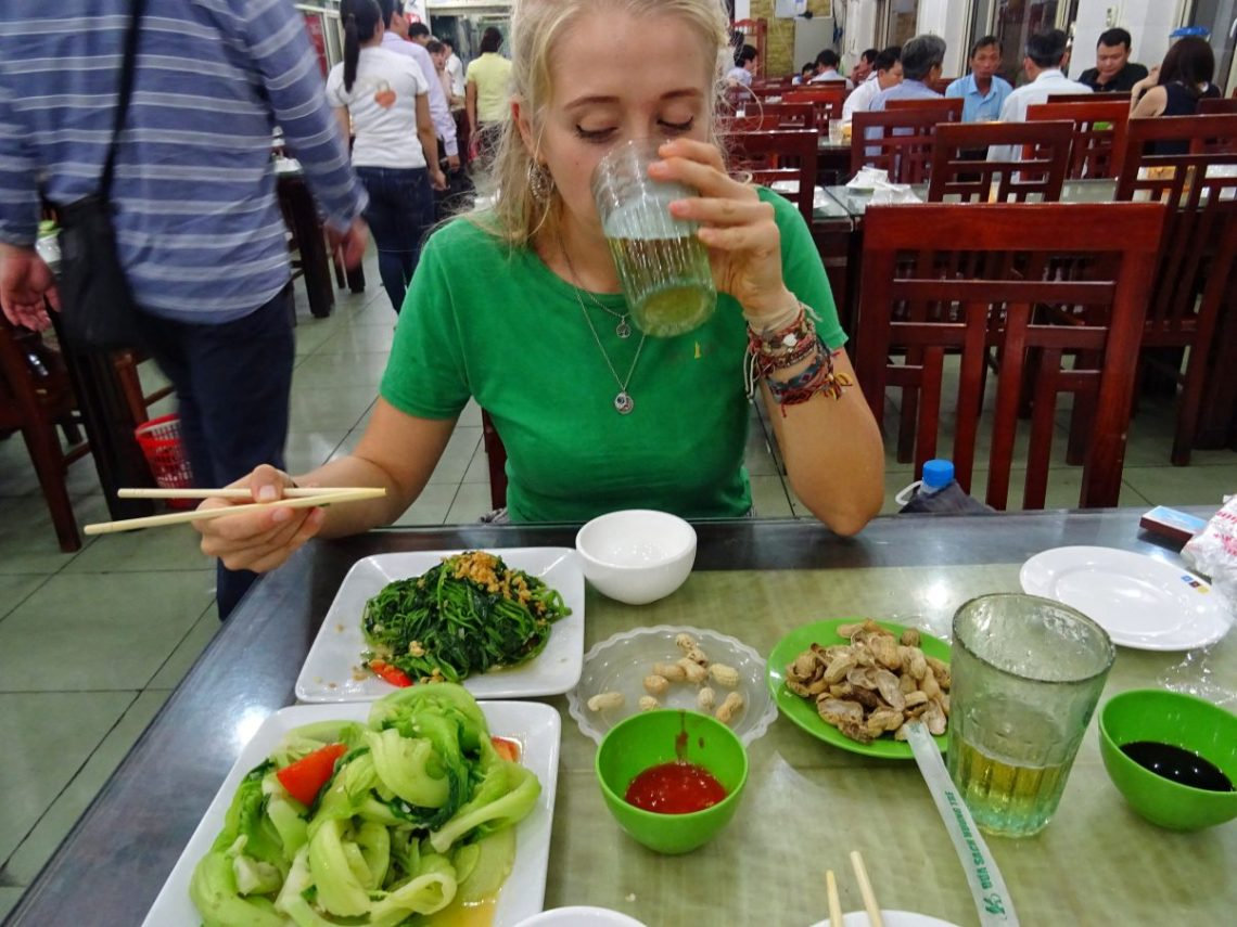 Girl eating and drinking in Bia Hoi Vietnam
