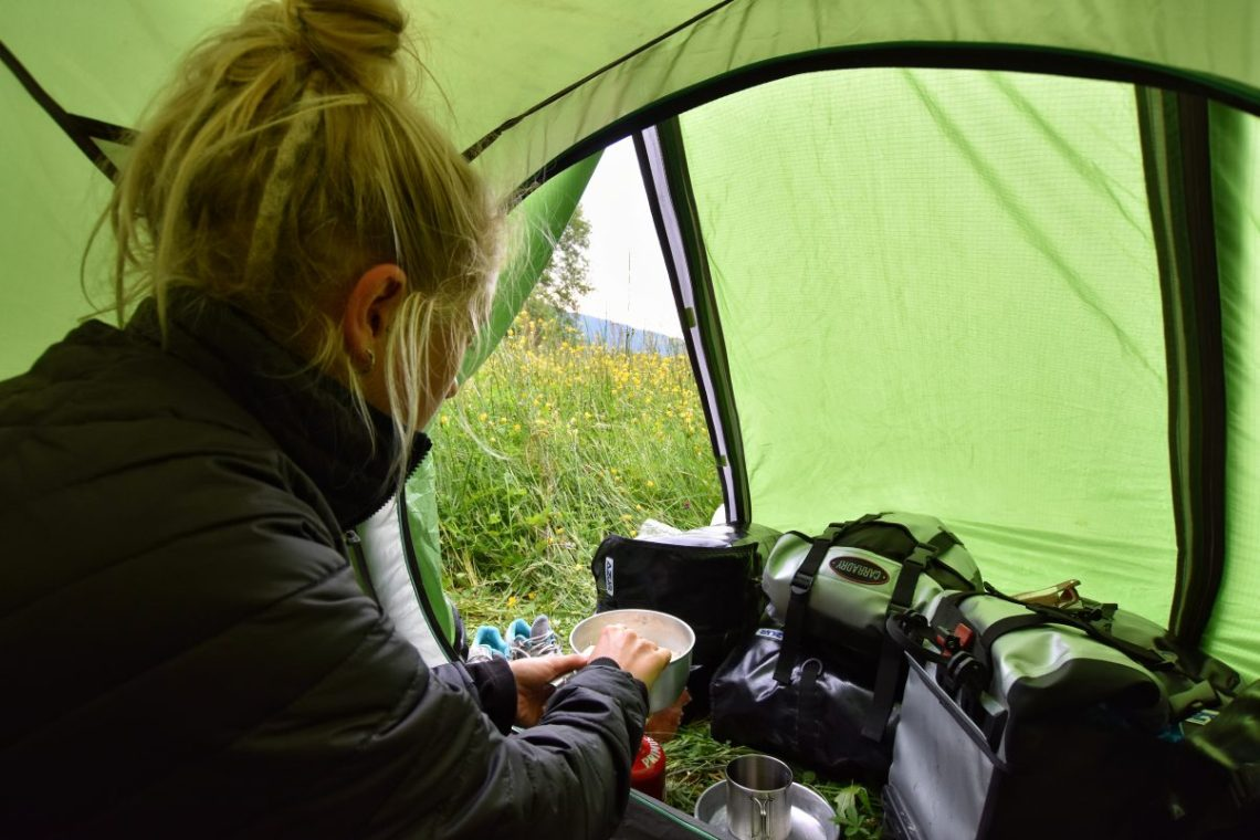 Girl camping and making food in tent