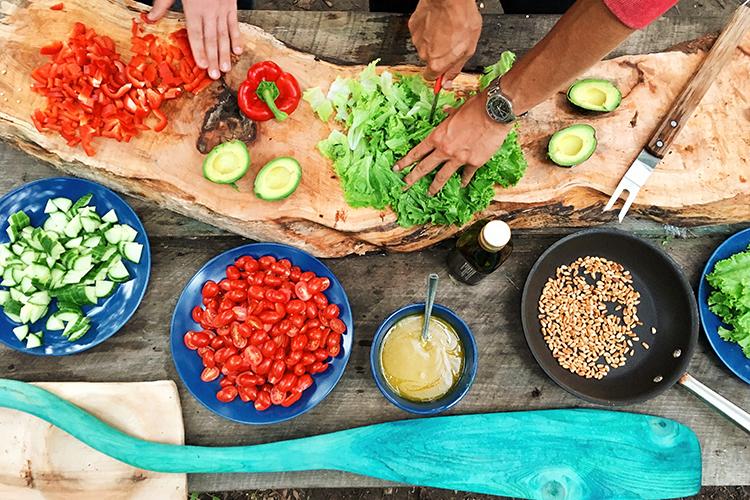 Grönsaker i skålar på en stor skärbräda