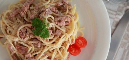 Vit tallrik med pasta carbonara sedd ovanifrån, till höger på tallriken en halverad cocktailtomat