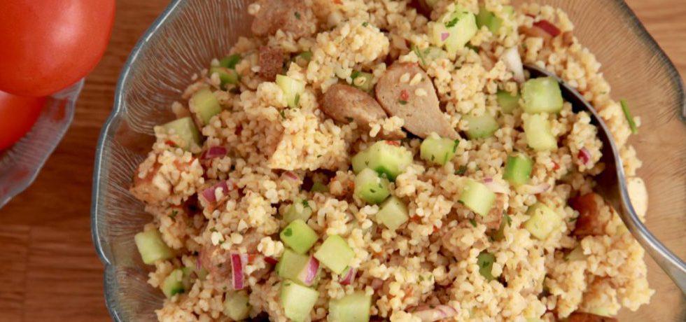 Bulgursallad med tärnad gurka, rödlök och sojaprotein i glasskål sett uppifrån