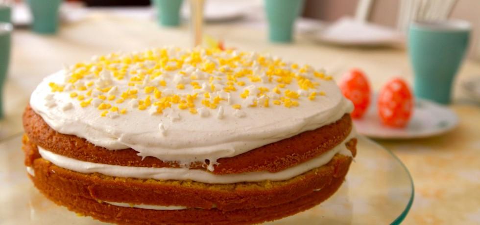 Tårta bestående av tre bottnar, grädde mellan och ovanpå och dekorerad med gult och vitt strössel. Påskägg och kaffekoppar i bakgrunden