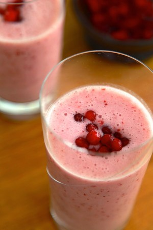 Två höga glas med rosa smoothie, toppade med lingon