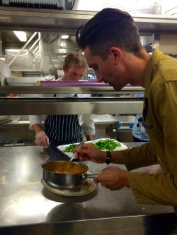 Maximilian häller sås över maträtt i köket på Birka